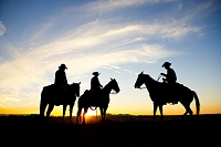 A silhouetted group of cowboys sit on a ridge line as the sun sets behind them.