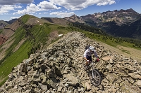 A mountain biker rides on a rocky trail through a talus field in the mountains.