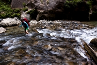 A woman uses a trekking pole to cross a section of the Virgin River during a backpacking trip through the Narrows in Zion National Park, in Springdale, Utah.