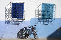 An abstract look at two windows and a bike in the coastal town of Asilah, Morocco.