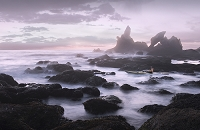 A sea kayaker paddles in a rock garden with sea stacks and arches at twilight. Region: Olympic Peninsula State: Washington Country: USA River/Ocean: Image 4991500017 is shot at Point of the Arches, Shi Shi Beach on the Olympic Peninsula.