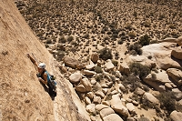 A female climber starts the dike traverse on Sidewinder (5.10b) in Joshua Tree National Park, California.