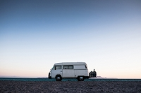A camper van sits on Tecelote Beach at sunrise in La Paz, Mexico.