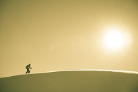 A skier crosses a snowy ridge in sunshine.