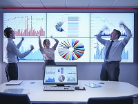 Business people celebrating success in front of graphs on screen