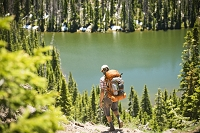 A backpacker hikes down a trail with an alpine lake in the distance.