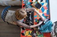 Overhead view of woman with vintage sewing machine selecting fabric