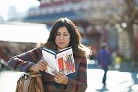 Mature female tourist reading guide book at Senso-Ji Temple, Asakusa, Tokyo, Japan