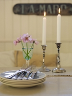 Close up of plates, cutlery and lit candles on dining table