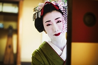 A woman dressed in the traditional geisha style, wearing a kimono and obi, with an elaborate hairstyle and floral hair clips, with white face makeup with bright red lips and dark eyes, looking in the mirror.