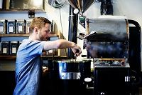 Young man putting in handful of coffee beans to coffee roaster in cafe