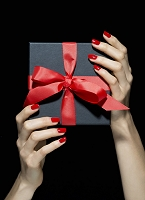 Woman's hands with red nail polish holding gift box