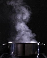 A steaming pot of water against a black background