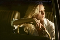 A woman wearing a white shirt sitting at the steering wheel of a car