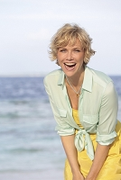 A blonde woman with short hair wearing a yellow dress and a mint-green, knotted blouse on a beach