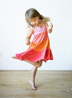 A little girl dancing in a ruffled dress
