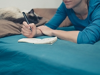 A young woman is lying in a bed with a cat and is taking notes with a pen and notepad