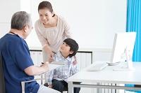 医師と診察を受ける男の子と母親