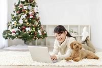 クリスマスツリーのあるリビングでパソコンをする女性