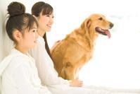 ペット壁にもたれて座る母娘とペットの犬
