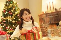 クリスマスプレゼントにリボンを結ぶ若い女性