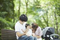 公園のベンチに座る日本人家族