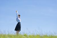 草原で伸びをする女子学生