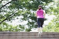 新緑の中でジョギングする女性