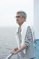 フェリーのデッキから海を見る中年男性