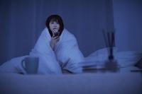 夜中にテレビ鑑賞をする日本人女性