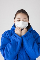 マスクをしてベンチコートを着る女性
