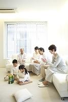 積木で遊ぶ子供達とソファに座り拍手をする両親と祖父母