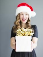 クリスマスのギフトボックスを持つ女性
