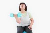 ダンベルを持つ肥満女性