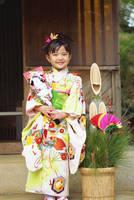 角松と羽子板を持つ晴れ着の女の子