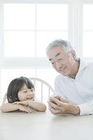 孫娘と携帯電話を見るシニア男性