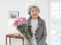 バラの花束を持つ日本人のシニア女性