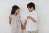 手を繋ぐ笑顔のハーフの男の子と女の子