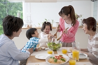 ダイニングテーブルで食事をする3世代家族