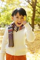 紅葉のきれいな秋の公園で遊ぶ子供