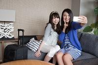 ホテルの客室でスマートフォンで撮影する女性