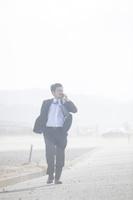 砂嵐の中電話をする日本人ビジネスマン