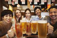 居酒屋で食事する日本人と外国人の若者たち