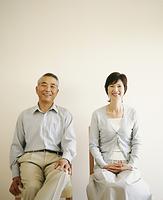 室内でイスに座る中高年夫婦
