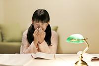 深夜の勉強中に咳をする女の子