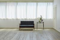 窓と黒いソファーとサイドテーブル