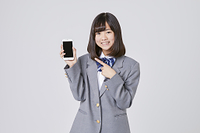 スマートフォンを持って指を指す女子中学生