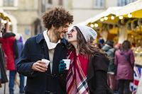 クリスマスマーケットで買い物するカップル