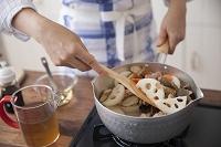 鶏肉と野菜を鍋で炒める女性