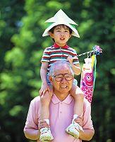兜をかぶりこいのぼりを持った孫と祖父